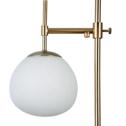 szklana biała kula w złotej lampie podłogowej