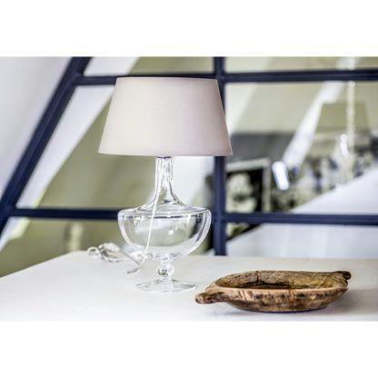 lampa stołowa ze szklaną, przezroczystą podstawą w oryginalnym kształcie i klasycznym, beżowym abażurem - aranżacja