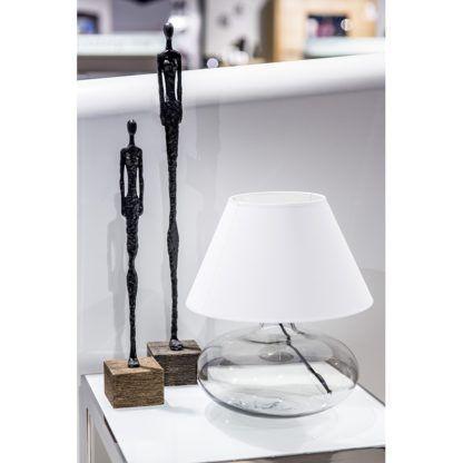 niska lampa stołowa z białym abażurem, bezbarwna podstawa ze szkła