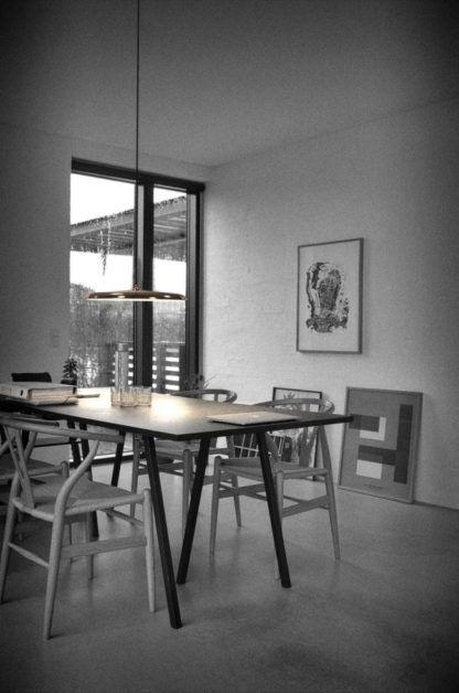 okrągła lampa wisząca z miedzianym, cienkim kloszem nad stół - aranżacja