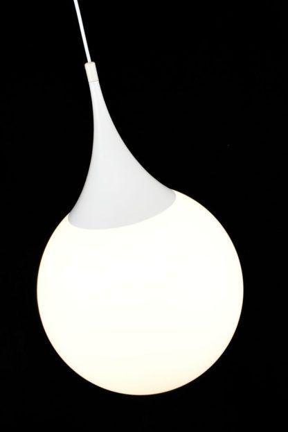 biała lampa szklana kula wiszaca nad stół