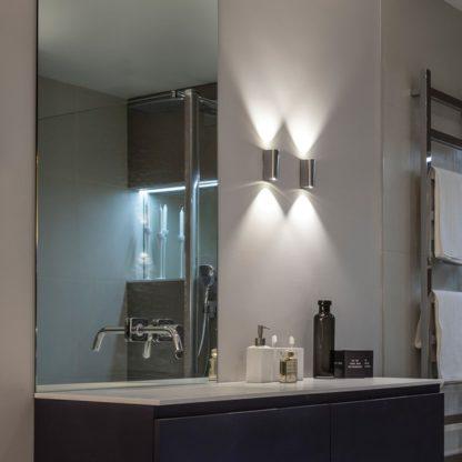 mały, pionowy kinkiet w srebrnym połysku, styl nowoczesny - aranżacja łazienka