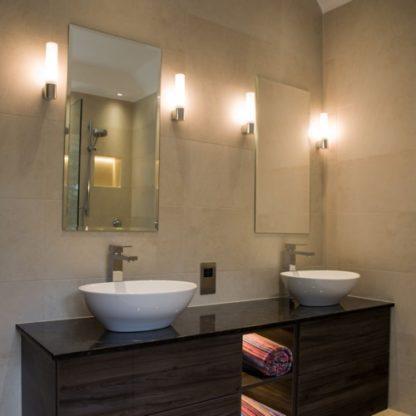 podłużny kinkiet łazienkowy z kloszem z mlecznego szkła i ze srebrną podstawą