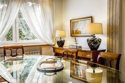 elegancka lampa stołowa z beżowym abażurem i szklana podstawą beżowo-czarną - aranżacja klasyczna jadalnia