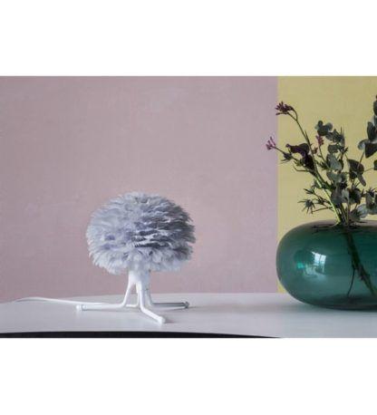 niewysoka lampa stołowa z szarym kloszem z piór, podstawa biały trójnóg, styl skandynawski - aranżacja pastele